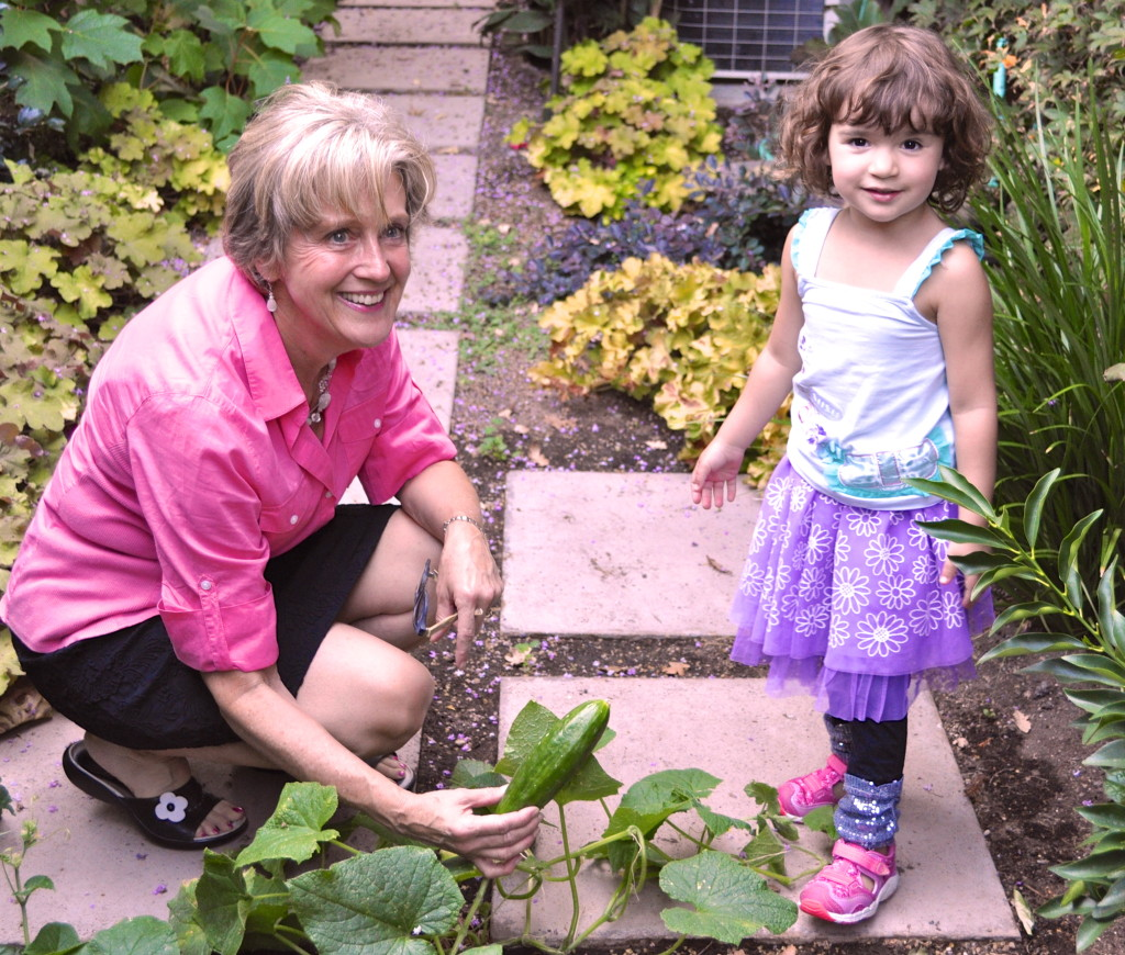 Lynne picking cucumbers with her granddaughter