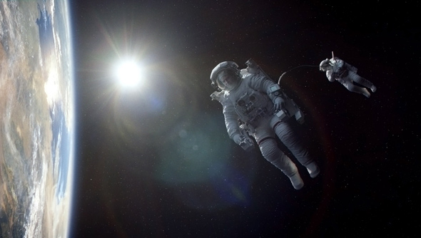 Astronauts George Clooney and Sandra Bullock floating in space in the film, Gravity.