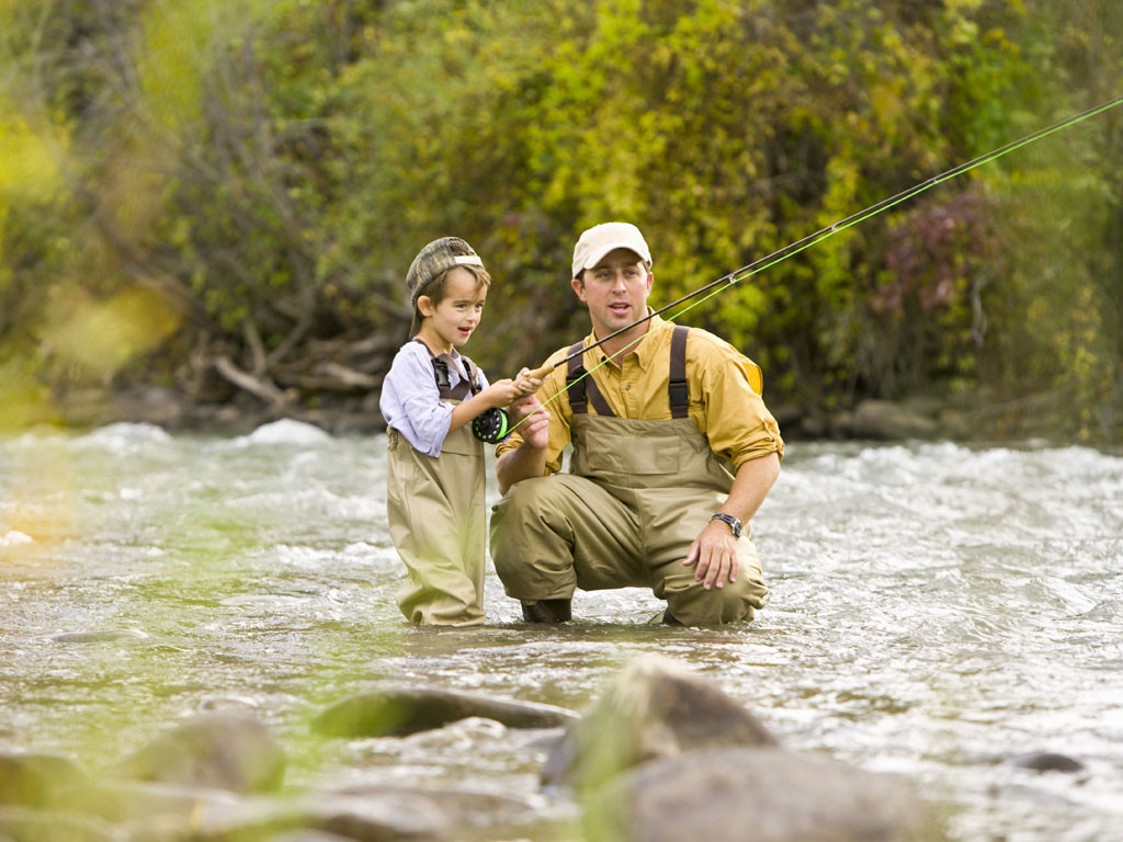 A Father teaching his son to fly fish in a bubbling river. Father's Day Gift Guide, Trueheartgal.